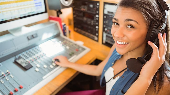 smiling woman with headphones on operating a new sound board