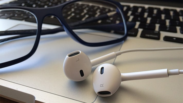 pair of glasses and apple headphones sitting on top of a macbook laptop