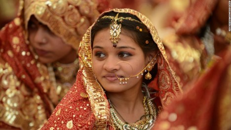 An Indian Muslim bride gestures during a mass wedding ceremony at the ancient Sarkhej Roja in Ahmedabad on February 22, 2013. Some 151 couples participated in a mass marriage organised by Hussaini Waqaf Committee. Participation in mass marriages in the Muslim and Hindu communities are on the rise against the 'Dowry System' in which huge donations are paid by the bride's family members to the family members of the grooms. Instead, in the mass marriages the brides are gifted with the basic necesitities of daily life. AFP PHOTO / Sam PANTHAKYSAM PANTHAKY/AFP/Getty Images