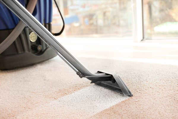 Cleaning service concept. Steam vapor cleaner removing dirt from carpet in flat, closeup