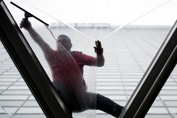 """FIRST PLACE:Philip Vukelich, University of Idaho (Shawn O'Neil, adviser) — Bold heights, new reflections. Miguel Martinez cleans a section of the glass roof overhang above the entrance to Swissôtel, Nov. 3. Martinez and his partner Cesar Gomez give many of the Chicago skyscrapers their reflective shine, including the Trump Tower. """"Working up there is amazing. At first I was scared. Everyone is when they start, but now I love it,"""" Gomez said, whose job regularly brings him hundreds of feet off of the ground into the Chicago skies."""