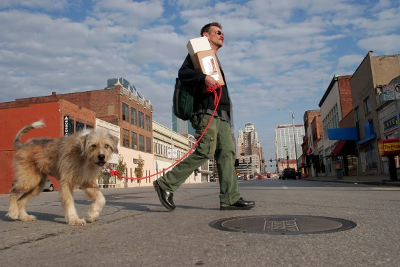 SECOND PLACE: Nick Loomis, University of Iowa — Kansas City resident Tom Deatherage walks his dog, Max, across Grand Blvd. on the way back to his art gallery after gathering salvaged materials for his artwork on Saturday morning.