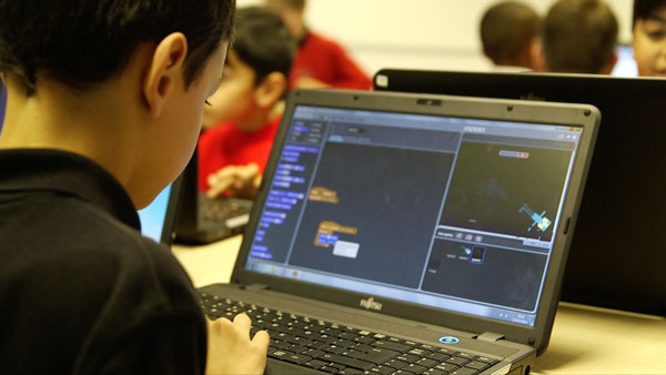 Boy coding on a laptop