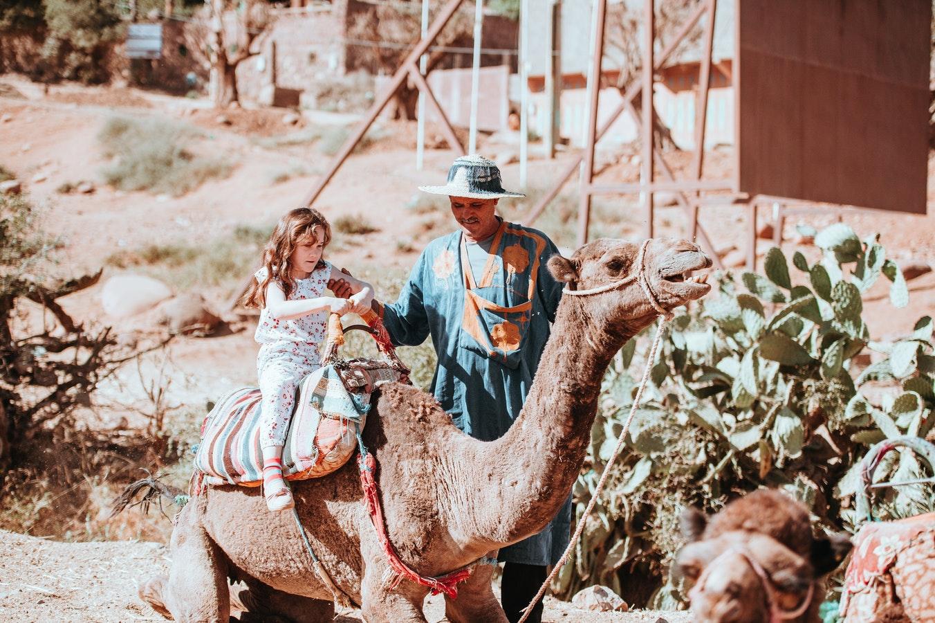 Photo d'une petite fille qui se promène à dos de dromadaire dans la nature marocaine