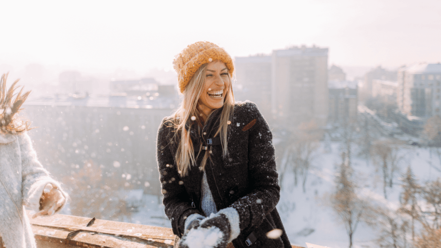 A woman smiling on her balcony with a look out over a snowy city, showing feelings in Polish