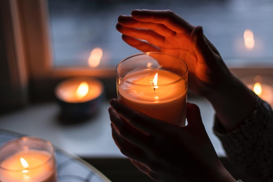 Woman holding hand up to a lit candle - how people get through winter