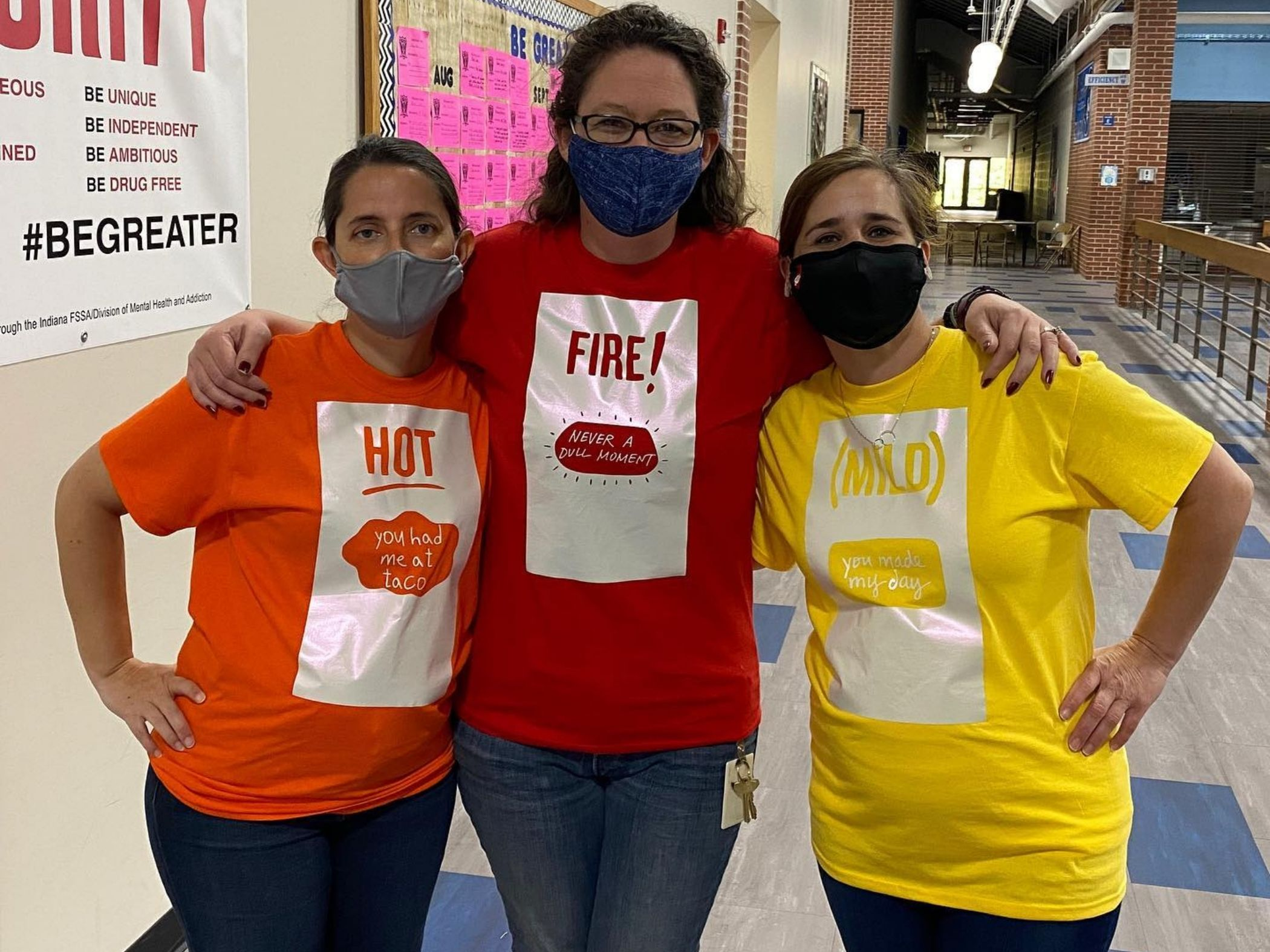 Staff members pose in costume as hot, fire and mild sauce packets