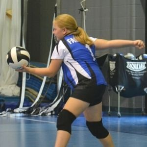 Student serving volleyball