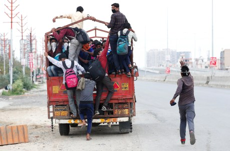 A migrant worker runs behind a truck as others try to board it to return to their villages.