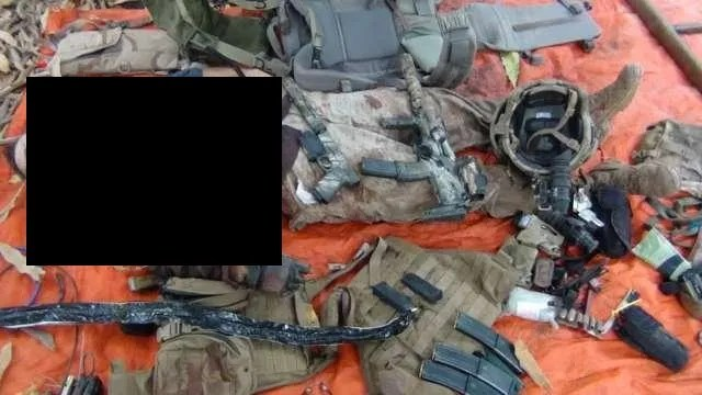 The fallen commando photographed by militants with his recovered weapons and gear.