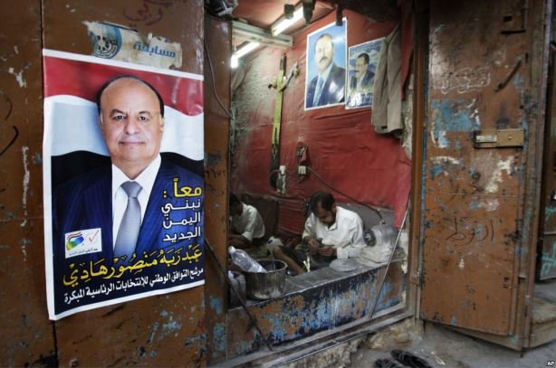 Men work in a shop while a poster of interim president Hadi hangs nearby