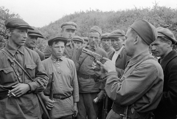 Soviet soldier showing Soviet partisans how to use the P-35.
