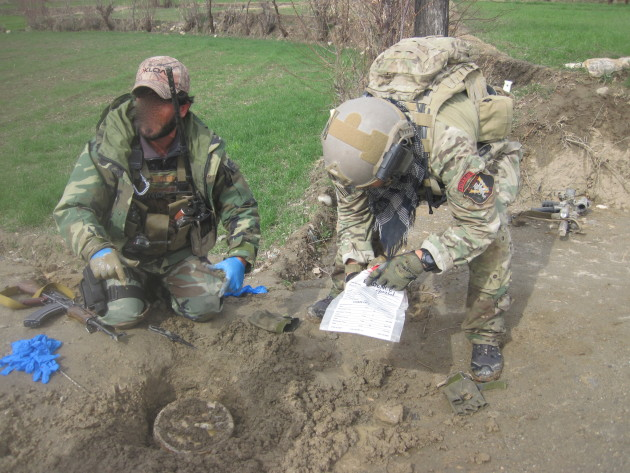 Third Special Forces Group (Airborne) Green Berets disarm an Improvised Explosive Device while on patrol during a recent tour of duty in Afghanistan. Many of the team members wore SOG Recon Team patches.