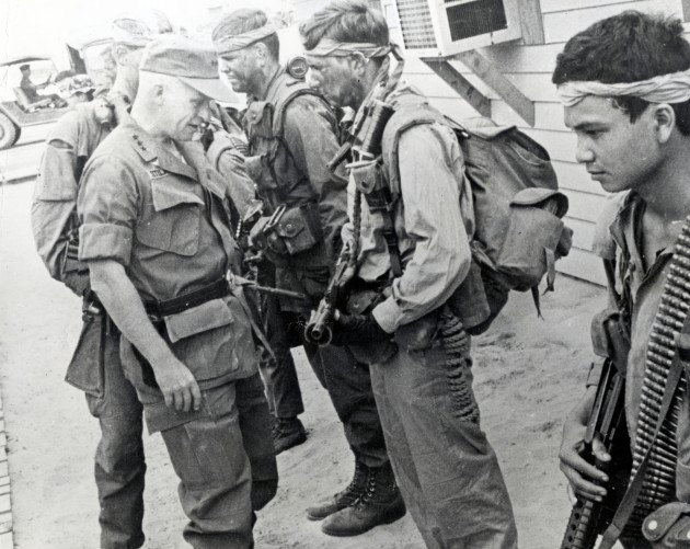 In April 1969, at CCN - the secret SOG compound in Da Nang, RT Idaho Green Beret Doug LeTourneau is queried by LTG Richard Stilwell, about a pending mission that RT Idaho was preparing to run in Laos. In the foreground is indigenous team member Cau, carrying 7.62 mm ammo for the M-60 machine gun and a CAR-15. To the right of LeTourneau is Capt. Michael O'Byrne. Stilwell inspected the team outside the CCN headquarters.