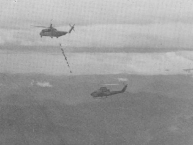 "An HMH-463 heavy-lift Marine Corps helicopter, YH-20, heads east with Marine crew members, Green Beret Medics SSG John ""Doc"" Padgett and Sgt. John Browne after a CH-53D had a crash landed due to enemy gun fire and a B-40 rocket hitting it. A Marine Corps Cobra gunship from HML-367 Scarface is escorting the big chopper. (Photo courtesy of Joe Driscoll)"