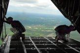 US Army Master Sgt. Dwight Simon and Staff Sgt. Monte Henderson watch for the drop zone from the ramp of a C-130