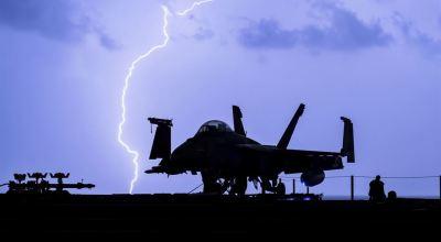 Lightning strikes near an F-18 Hornet on the USS Theodore Roosevelt