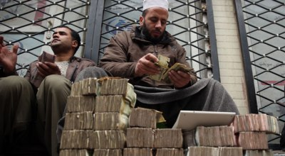 Featured image: Afghan money changer, right, counts a pile of currency at the Money and Exchange Market in Kabul, Afghanistan, Monday, Jan. 12, 2015. The Afghanistan's currently, afghani, stands at 57.60 against the U.S. dollar.  AP Photo/Massoud Hossaini