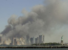 The Statue of Liberty, right, stands at the entrance to New York Harbor as the twin towers of the World Trade Center burn in this view from Jersey City, N.J., Sept. 11, 2001. (AP Photo/Mike Derer)
