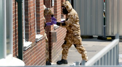 Emergency workers in military protective suits search the fenced off John Baker House for homeless people on Rollestone Street in Salisbury, England, Friday, July 6, 2018. British police are scouring sections of Salisbury and Amesbury in southwest England, searching for a container feared to be contaminated with traces of the deadly nerve agent Novichok. (AP Photo/Matt Dunham)