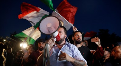Far-right wing Casapound's activists wave Italian flags in Rocca di Papa, near Rome, Tuesday, Aug. 28, 2018. Approximately 100 refugees and migrants who disembarked from the Italian coast guard ship 'Diciotti' on Sunday after a ten days standoff are expected to arrive in Rocca di Papa reception center on Tuesday evening. (AP Photo/Gregorio Borgia)