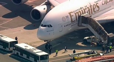 In this frame from video, a person walks off an Emirates plane at JFK International Airport to a waiting bus on Wednesday, Sept. 5, 2018, in New York, as emergency response crews gather outside the plane amid reports of ill passengers aboard a flight from Dubai. (WABC 7 via AP)