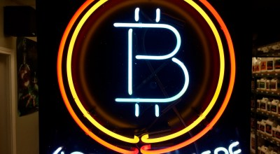 A neon sign hanging in the window of Healthy Harvest Indoor Gardening in Hillsboro, Ore., shows that the business accepts bitcoin as payment (AP).