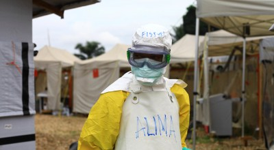 In this photo taken Sunday, Sept 9, 2018, a health worker sprays disinfectant on his colleague after working at an Ebola treatment centre in Beni, Eastern Congo. The current Ebola outbreak in northeastern Congo has become a testing ground with one aid group for the first time treating confirmed Ebola victims in individual biosecure units used in emergencies involving highly infectious diseases/ (AP Photo/Al-hadji Kudra Maliro)
