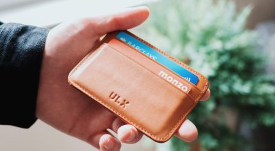 Person holding brown ULX leather wallet/ Oliur on Unsplash