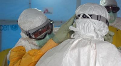 This image was captured in Monrovia, Liberia's capital city, during the 2014 West African Ebola virus disease outbreak that also affected Sierra Leone, Guinea and Nigeria. Here Dr. Joel Montgomery, team lead for the U.S. Centers for Disease Control and Prevention Ebola Response Team in Liberia, is dressed in his personal protective equipment while adjusting a colleague's PPE before entering the Ebola treatment unit, which opened on August 17, 2014. This treatment unit is staffed and operated by members of Médecins Sans Frontières (MSF), or Doctors Without Borders. CDC photo by Athalia Christie via defense.gov