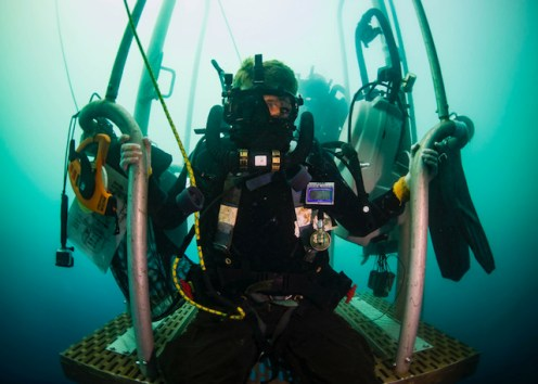 U.S. Navy Diver 1st Class James Mostek, assigned to Mobile Diving and Salvage Company ONE-SIX, embarked aboard USNS Salvor (T-ARS 52), waits on a diving stage during a two-hour decompression stop after diving to 240 feet off the coast of Madang, Papua New Guinea, Dec. 7, 2018. The sailor is completing a Defense POW/MIA Accounting Agency (DPAA) underwater recovery mission searching for personnel who went missing during WWII. DPAA conducts global search, recovery and laboratory operations to provide the fullest possible accounting for our missing personnel to their families and the nation. (U.S. Navy Photo by Mass Communication Specialist 1st Class Tyler Thompson)