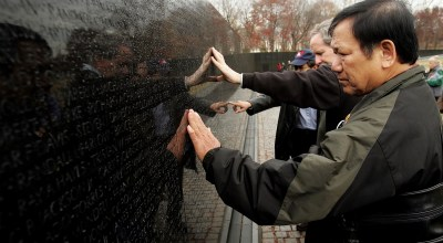 WASHINGTON - NOVEMBER 28: Former United States Marine Frank Corcoran (L), a member of Veterans for Peace, and Ho Sy Hai (R), a veteran of the North Vietnamese Army, search for names while touring the Vietnam War Memorial Wall during an event bringing together victims of the use of Agent Orange, a defoliant widely used by the U.S military in the war in Vietnam November 28, 2005 in Washington, DC. In 1991 U.S. veterans of the War in Vietnam won limited disability benefits for certain illnesses caused by Agent Orange though Vietnamese victims have not. Corcoran has suffered from prostate cancer; Ho Sy Hai has suffered from chronic hepatitis, ulcers, enterolitis, and prostate cancer. (Photo by Win McNamee/Getty Images).