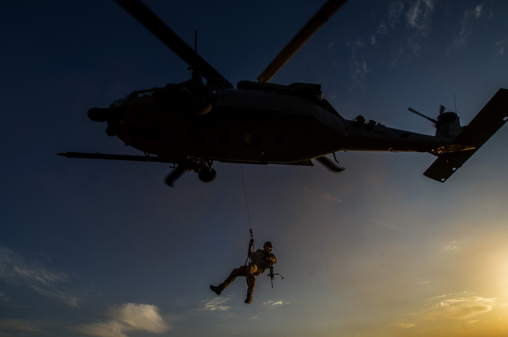 U.S. Air Force pararescueman lowered from a HH-60 Pave Hawk.