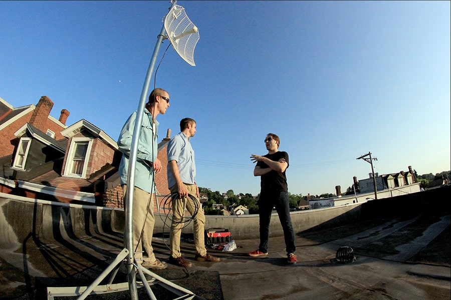 Image of people on a roof with an antenna