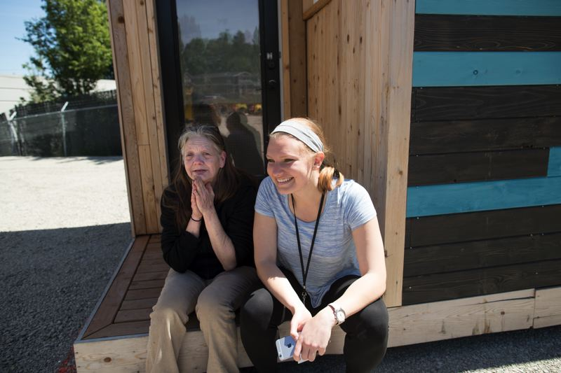 PORTLAND TRIBUNE: JAIME VALDEZ - Debbie Haskett (left), a new resident of Kenton Women's Village, and her caseworker, Bernadette Stetz (right), sit on the porch of one of the 14 tiny homes that make up Kenton Women's Village. Haskett has been homeless since 2009 and spent many of those years camping in and around the Kenton neighborhood; Stetz hopes to help her find permanent housing this year.