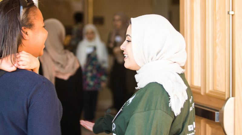 PHOTO COURTESY WHITNEY GOMES, - Hanan Al-Zubaidy, above right, greets a guest at a community interfaith event she helped organize, the Ramadan Tent Project open iftar.