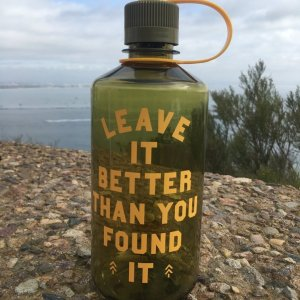A green translucent water bottle with yellow writing. The writing says Leave It Better Than You Found It.