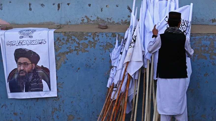 بائع أفغاني يفحص أعلام طالبان بجانب ملصق لزعيم طالبان عبد الغني بارادار على طول شارع في كابول - 27 أغسطس 2021