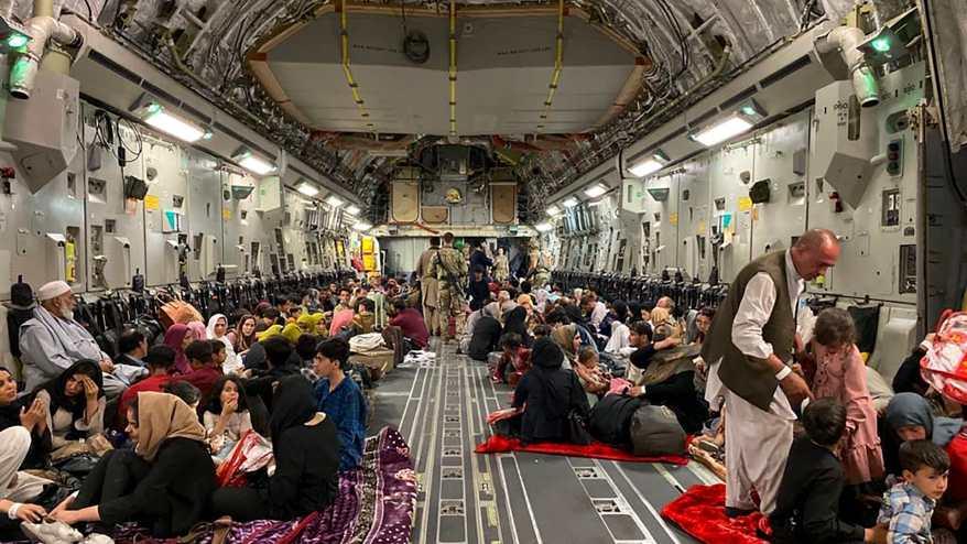 أفغان يجلسون داخل طائرة عسكرية أمريكية لمغادرة أفغانستان، في المطار العسكري في كابول في 19 أغسطس 2021