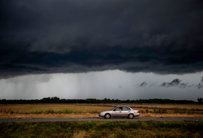"""Huracán Laura Hurricane Texas Louisina A car drives under an ominous rain cloud from tropical storm Marco as locals prepare for the arrival of hurricane Laura near Lake Charles, Louisiana on August 25, 2020. - Storm Laura was upgraded to a destructive hurricane on August 25 and is forecast to make landfall along the Texas or Louisiana coasts on Wednesday night, after earlier causing 20 deaths in Haiti.""""Laura has become a hurricane with maximum sustained winds of 75 mph (120 km/h), with higher gusts,"""" the US National Hurricane Center reported. (Photo by Andrew CABALLERO-REYNOLDS / AFP) (Photo by ANDREW CABALLERO-REYNOLDS/AFP via Getty Images)"""