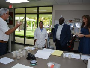 In the mosquito counting lab: (L-R) Jim McNelly and Zoila Ebanks of the MRCU, Minister Dwayne Seymour and Chief Officer Jennifer Ahearn