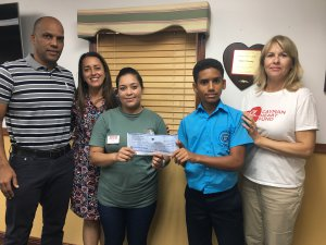 Brandon Simmonds presents donation to Anthony's mother, Rosa Martinez-Vaquedano, with (L-R) the student's parents, Marcus and Monique, and Colleen Mellott of Cayman Heart Fund