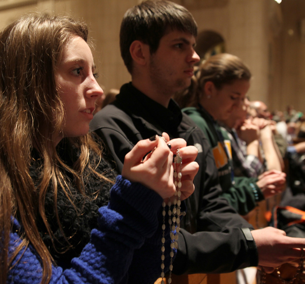 Young people with rosaries pray during the National Prayer Vigil for Life at the Basilica of the National Shrine of the Immaculate Conception in Washington Jan. 21. (CNS/Bob Roller)