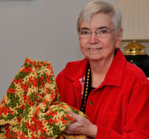Mercy Sister Mary Ann Walsh takes comfort in a prayer shawl given to her by a former colleague in this 2014 photo taken at the Mercy Motherhouse in Albany, N.Y. (CNS/courtesy Northeast Communications for Sisters of Mercy)