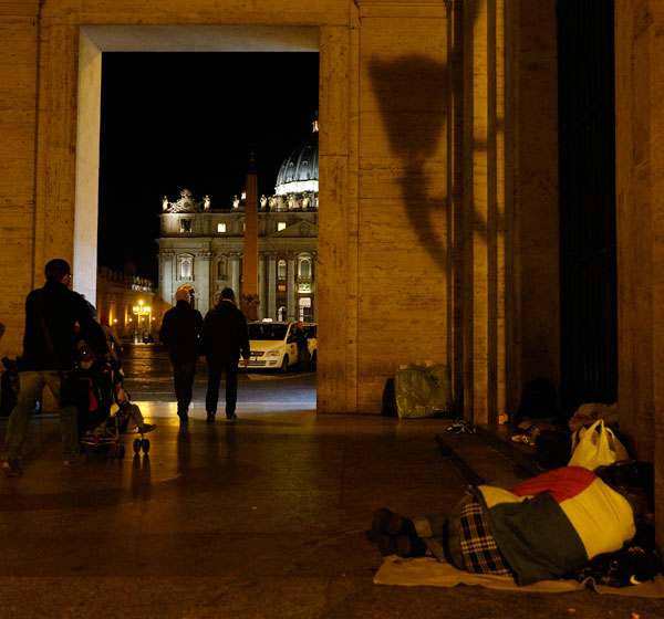 A homeless person sleeps outside the Vatican press office near St. Peter's Square last November. (CNS/Paul Haring)
