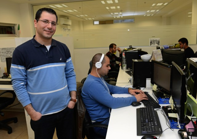 Joseph Karkaby, a software team leader at Galil Software in Nazareth, Israel, stands near workers in his office.  (CNS/Debbie Hill)