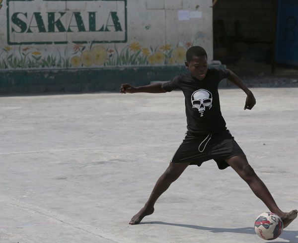 A boy plays soccer at the SAKALA community center in the Cite Soleil neighborhood of Port-au-Prince, Haiti. He participates in the SAKALA program, a peacebuilding program for youth sponsored by Pax Christi Haiti. (CNS/Bob Roller)