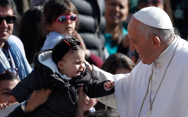 Pope Francis greets a baby as he arrives to lead his general audience in St. Peter's Square at the Vatican March 18. (CNS/Paul Haring)