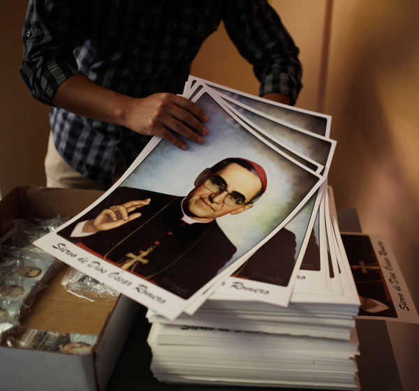 A volunteer holds posters of slain Salvadoran Archbishop Oscar Romero at a church in San Salvador Feb. 3, the day Pope Francis officially recognized the prelate's martyrdom. (CNS/Reuters)
