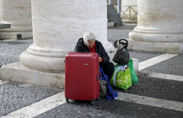 A homeless woman sits with her belongings as she waits for a friend leaving the Vatican in March. (CNS/Reuters)